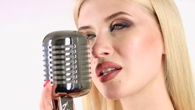 Singer sings in a retro microphone. White background. Side view. Close up. Singer sings in a retro microphone, her voice is gentle and the goose bumps from the stock video footage
