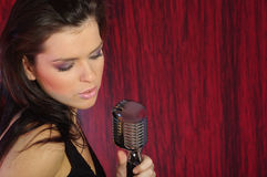 Singer on stage. Girl Singing In The Retro Microphone Royalty Free Stock Photography