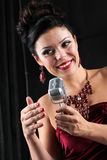 Singer on stage with spotlight Stock Images