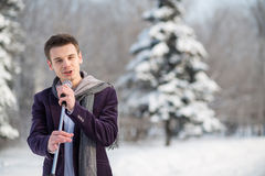 Singer in a suit and a scarf sing holding a microphone. The singer in a suit and a scarf sing holding a microphone outdoors in winter Royalty Free Stock Image