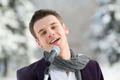 The singer in a suit and a scarf sing outdoors Royalty Free Stock Photos