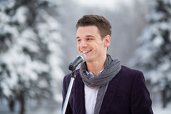 The singer in a suit and a scarf stands outdoors Stock Photos