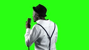 Singer the view from the back sings into a retro microphone and dancing near it. Green screen. Slow motion. Close up stock video footage
