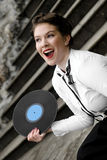 Singer with vinyl record. Young attractive women dressed in forties style, swing era, holding vinyl record Stock Photography