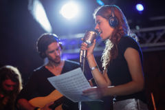Singer wearing headphones while singing at nightclub. Female singer wearing headphones while singing at nightclub Royalty Free Stock Image