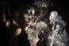 Singer woman with retro microphone in smoke Royalty Free Stock Image