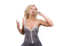 Singer. Young woman singing into microphone. Royalty Free Stock Photo