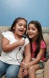 Singers II. Two little girls singing together Stock Photo