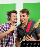 Singers With Microphone And Guitar Performing In Recording Studi. Male singers with microphone and guitar performing in recording studio Stock Photo