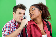Singers Performing In Recording Studio. Excited male and female singers performing in recording studio Royalty Free Stock Photography