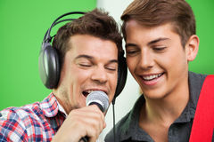 Singers Performing In Recording Studio. Happy male singers performing in recording studio Stock Photos
