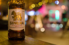 Singha beer. BANGKOK, THAILAND - SEPTEMBER 24, 2016: A bottle of Singha beer locate on the table with blur background Stock Photography