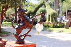 Singha Thai mythical creature with lamp in the garden. Stock Image