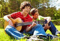 Singing. Portrait of happy lad playing the guitar with his friend near by Stock Photo