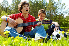 Singing. Portrait of happy lad playing the guitar with his friend near by Stock Image