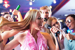 Singing. Portrait of joyous girl singing at party on background of happy friends Royalty Free Stock Image