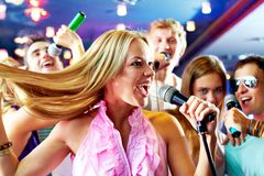 Singing. Portrait of joyous girl singing at party on background of happy friends Stock Photo