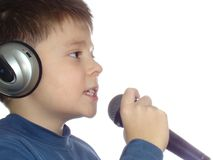 Singing. Boy using microphone and with headphones isolated over white Stock Image