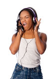 Singing along while listening to music. Beautiful teenager happily singing along jamming while listening to music, on white Stock Photography