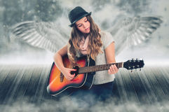Singing Angel. Portrait of a beautiful girl with a guitar, behind which the wings Royalty Free Stock Photos