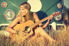 Singing. Attractive blonde woman on a field singing and playing guitar Royalty Free Stock Photos