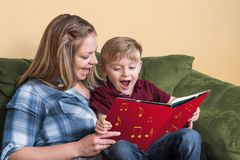 Singing with a book. A young child gets ready to read by singing with his mother using a book based on a song royalty free stock image