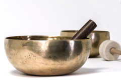 Singing bowl with mallets. Two bronze copper alloy singing bowls with one hitting and one rubbing mallets on white background Stock Photos