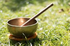 Singing bowl in the own garden, zen outdoors. Metal singing bowl in the grass of the own garden, zen wellness massage buddhism yoga alternative medicine nature stock photo
