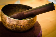 Singing Bowl on a Pillow with Wand. Engravings on the inside of a brass singing bowl start to oxidize and turn some cool colours Royalty Free Stock Photo
