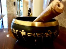 Tibetan Singing Bowl with wooden striker. A singing bowl is played with a wooden mallet sometimes called a wand or puja is rotated around the outside rim to royalty free stock image
