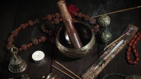 Singing bowl, prayer beads, prayer drum, stone balls and other Tibetan religious objects for meditation. And alternative medicine on a brown wooden background stock footage