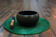 Singing bowl. Tibetan singing bowl on green decorative placemat Stock Photos