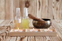 Singing bowl on wooden background. Burning candles and oil for aromatherapy and massage. stock image