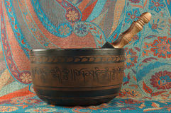 Singing bowls. Metal Tibetan singing bowl against the backdrop of Indian fabrics stock image