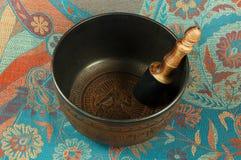 Singing bowls. Metal Tibetan singing bowl against the backdrop of Indian fabrics Stock Photography