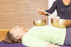 Singing bowls. A women is relaxing with singing bowls on her body royalty free stock image