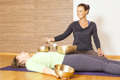 Singing bowls. A women is relaxing with singing bowls on her body royalty free stock images