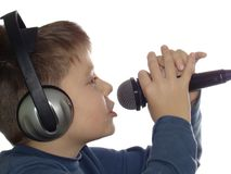 Singing boy. Using microphone and with headphones isolated over white Royalty Free Stock Image