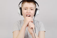 Singing boy. In headphones with copy space stock images