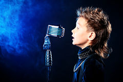 Singing boy. Emotional little boy is singing into a microphone like a rock musician stock images
