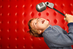 Singing boy with microphone on rack against wall. Singing boy with microphone on rack against red wall. Horizontal format royalty free stock photos