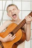 Singing child playing guitar in shower stall Royalty Free Stock Image