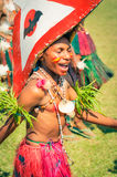 Singing and dancing boy in Papua New Guinea. Hagen show, Papua New Guinea - circa August 2015: Young half-naked boy wears pink skirt and large red and white hat stock images