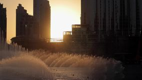 Singing fountains at evening sunset near Burj Khalifa. Dubai fountain near Burj Khalifa illuminated by the city at sunset stock video