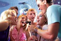 Singing friends. Portrait of joyous guys and girls singing at party in one microphone Royalty Free Stock Photos