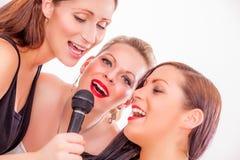 Singing friends of karaoke. Singstar band fun girls singing around the clock Stock Images