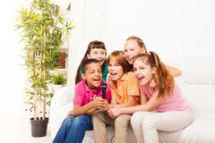 Singing is fun. Group of five happy diversity kids, boys and girls, singing together sitting on the coach in living room Stock Photo