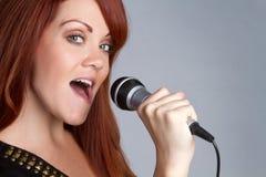 Singing Girl. Pretty redhead girl singing karaoke Royalty Free Stock Image