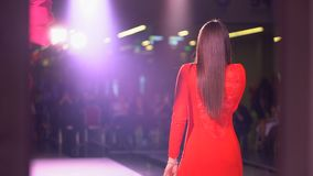 Singing girl artist in red dress on scene, Back view of girl singer in stage lights. Young woman singing song on live stock video