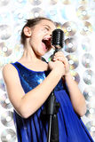 Singing girl. The girl in a blue dress singing karaoke Royalty Free Stock Photography